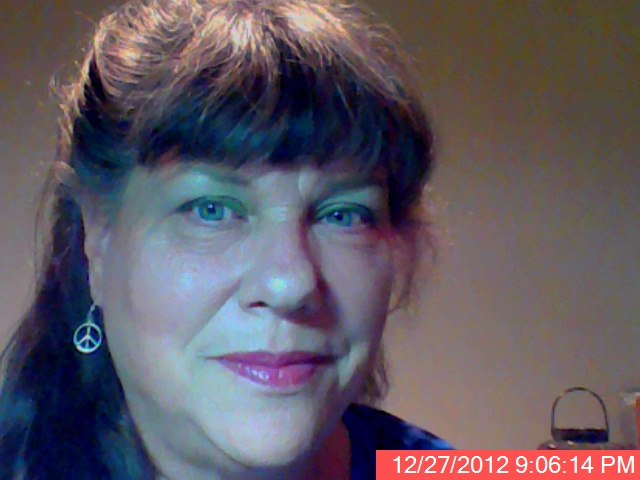 Debra has long dark hair with bangs and wears silver peace symbol earrings.