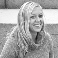 black-and-white-photo-of-a-smiling-blond-young-woman-wearing-a-sweater