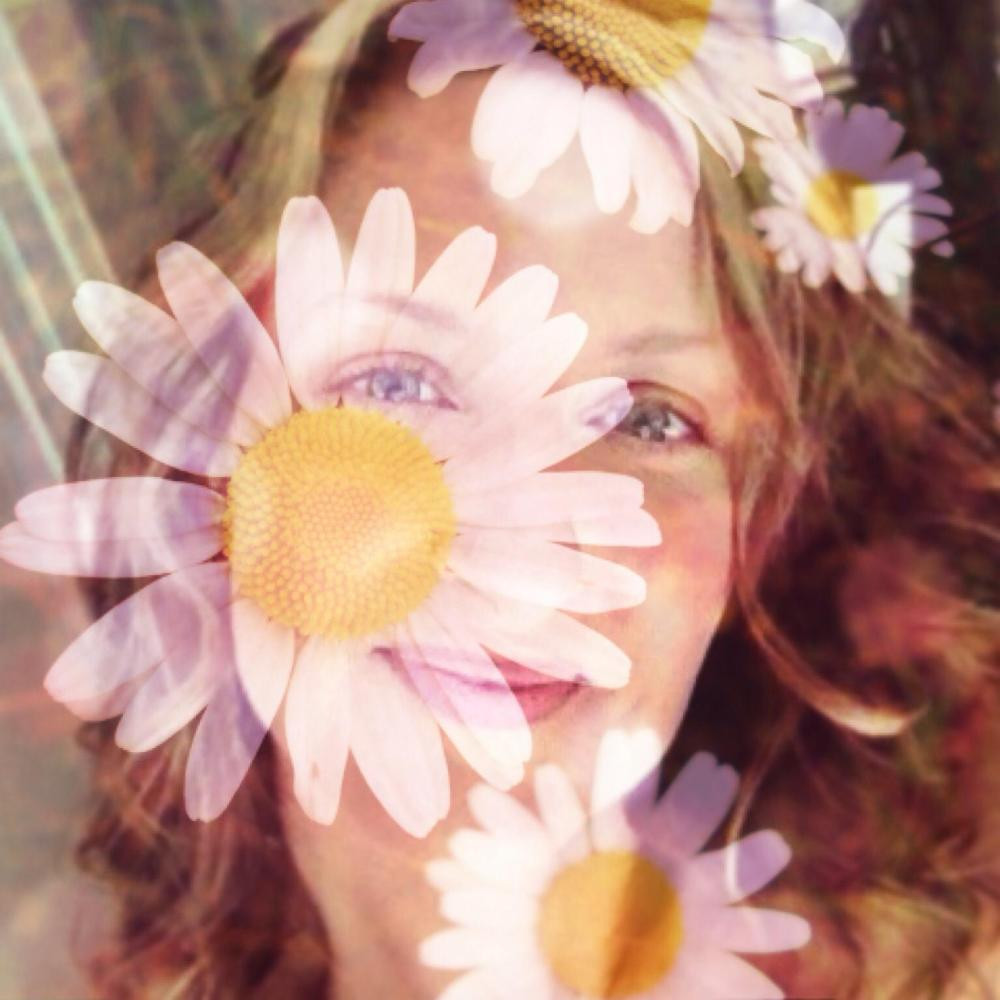 blond-hazel-eyed-woman-behind-a-transparent-layer-of-daisies
