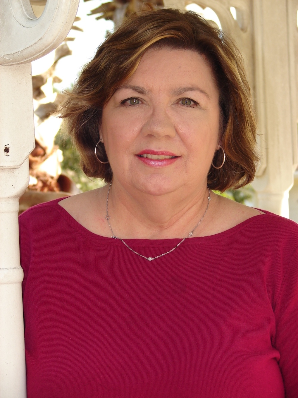 Headshot of middle aged woman  with chin length brown hair wearing magenta sweater posed outdoors.