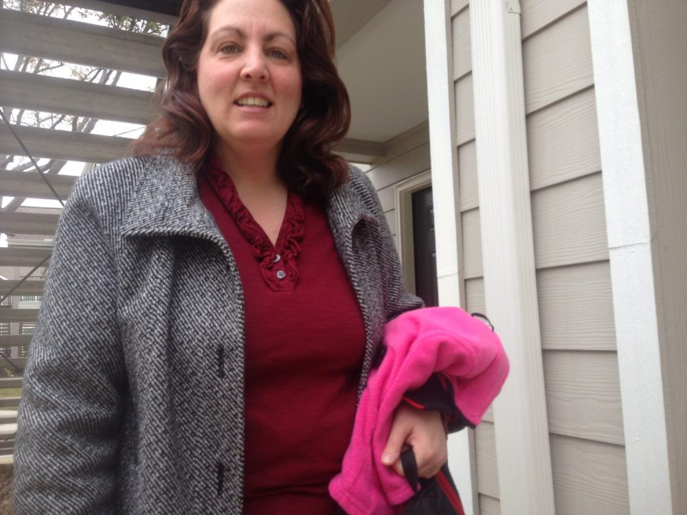 Woman on a porch with a grey coat on, unbuttoned. She wears a red shirt and holds a pink fleece. She's looking and smiling at the camera.