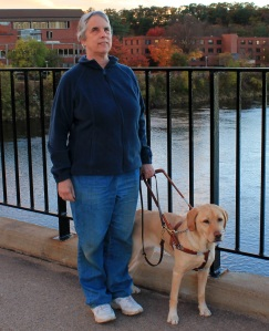 Kathie and her Seeing Eye dog walking across a bridge with fall foliage in the background.