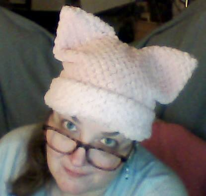 "Photo taken from above, a woman smiles up at the camera. She's wearing glasses and a light pink ""pussy"" hat."