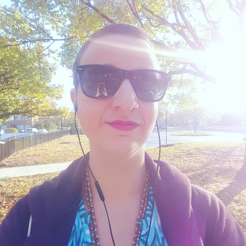 Woman with buzzed haircut stands outside with headphones and sunglasses. She smiles at the camera, and her phone is reflected in her sunglasses. It's a sunny day.
