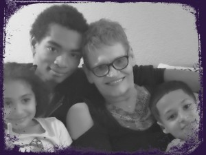 Four people sitting together on a couch, from left to right a girl, a young man, an older woman with short hair and glasses, and a young boy, all embracing