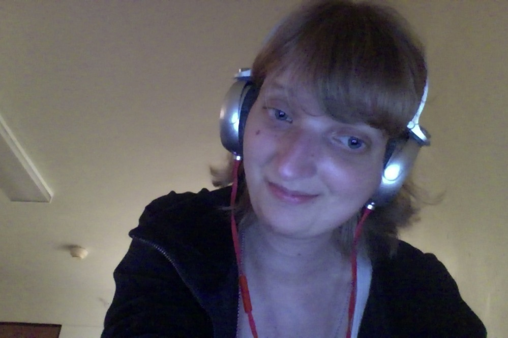 White woman with short blonde hair wearing headphones and a black jacket, smiling and looking slightly away from the camera and to the right.