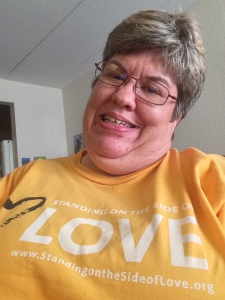 A woman with glasses and short gray hair wearing a yellow t-shirt that says LOVE