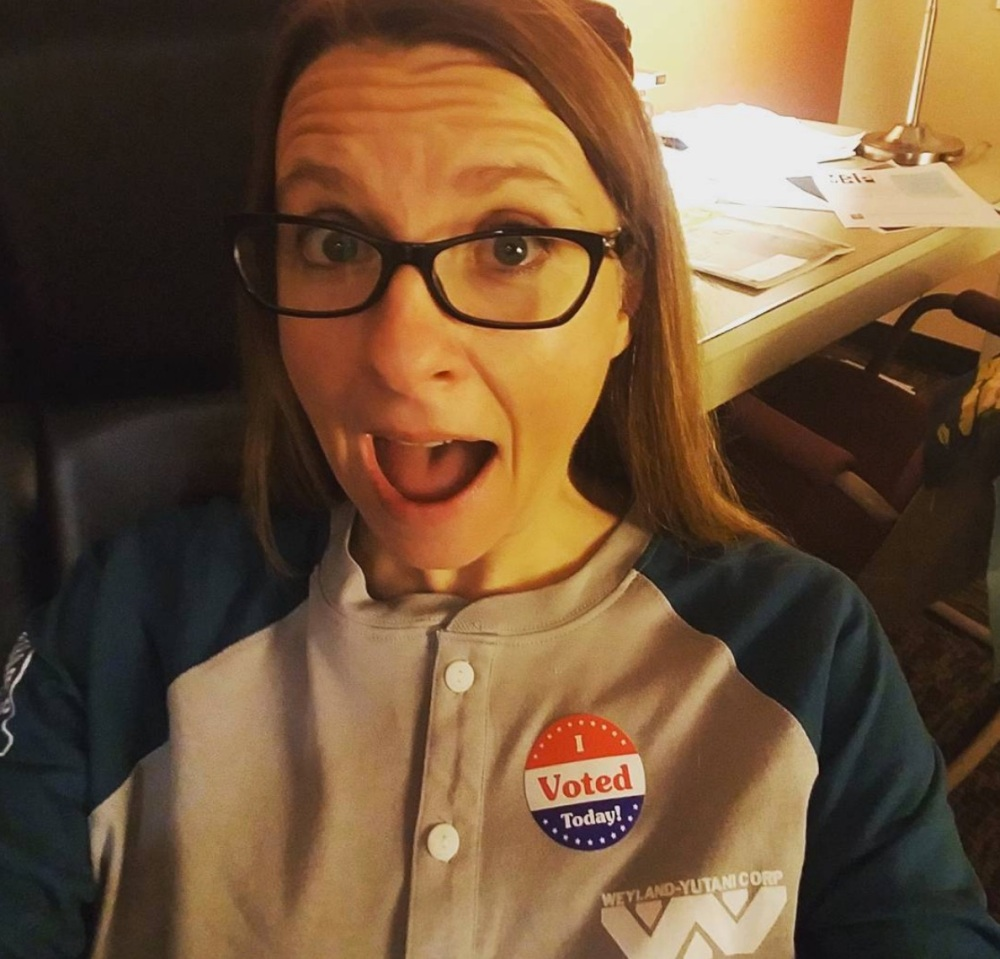 "Woman with long, light brown hair wears glasses and looks at the camera with her mouth open. She wears a button-up raglan sleeve shirt with a sticker that says ""I Voted."""