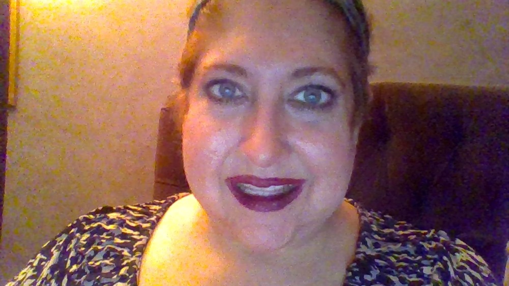 Me smiling, wearing dark pink lipstick, short hair pulled back, wearing a black and white shirt.