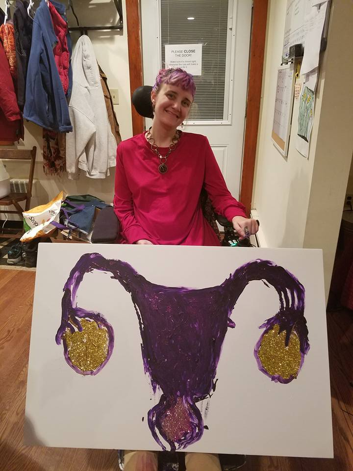 Woman with purple and pink hair sitting in her wheelchair holding a painting of a sparkly uterus and vagina.