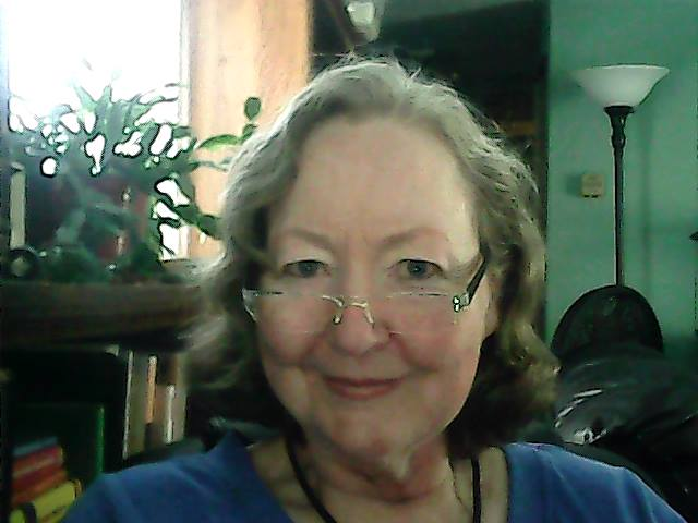 Headshot of Lynda indoors, near a window which is full of light. There's a succulent plant to her right and she looks over her glasses directly at the camera.