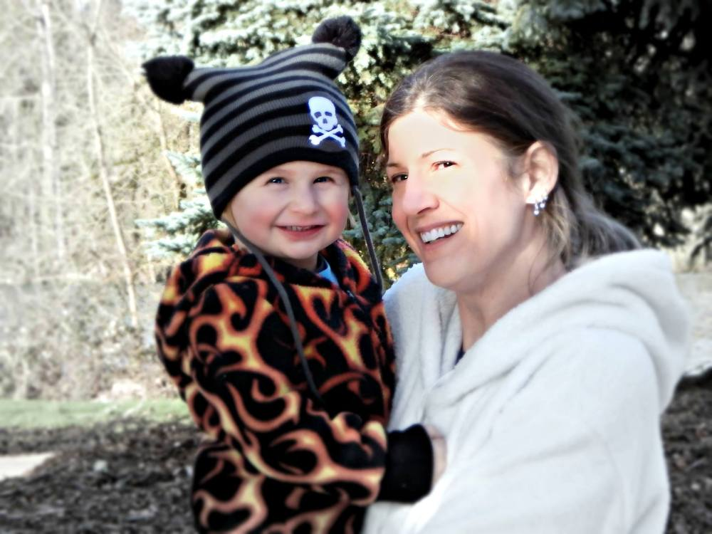 Woman wearing a white fleece smiles into the sun and holds a child in her arms. The child wears a fleece with a flame pattern and a striped black hat.