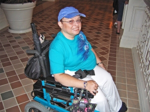 A person in a turquoise t-shirt and blue baseball cap and glasses sitting in a power chair