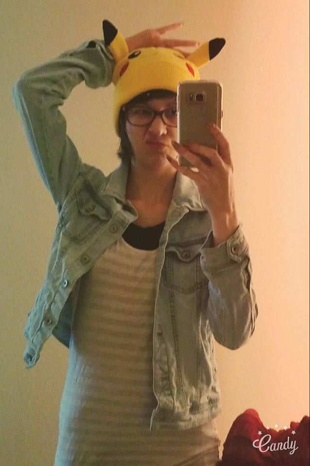 Woman holding up her phone takes a selfie in a mirror. She's wearing a jean jacket and yellow Pokemon hat.