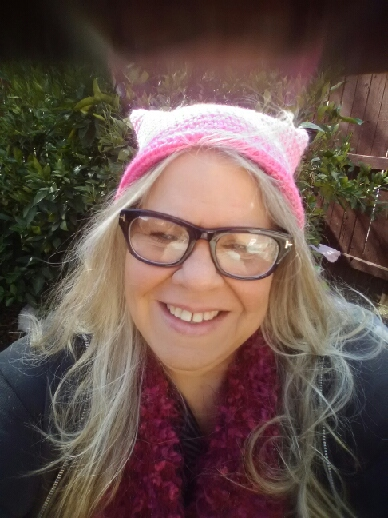 A woman with long blonde hair and glasses, wearing a pink pussy hat, sits in a purple chair in her garden with the smile of solidarity on her face.