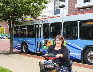 Me on my local bus website, sitting on power scooter in front of a bus