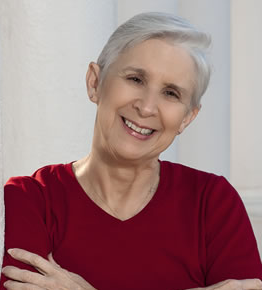 A woman with short gray hair and a red shirt, her arms folded in front of her, smiling
