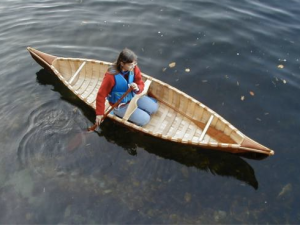 A woman sitting in a canoe in the water, seen from above
