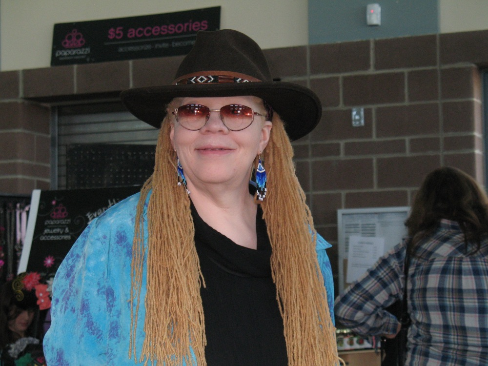 Woman with golden hair and blue earrings wears a black hat and tinted glasses.
