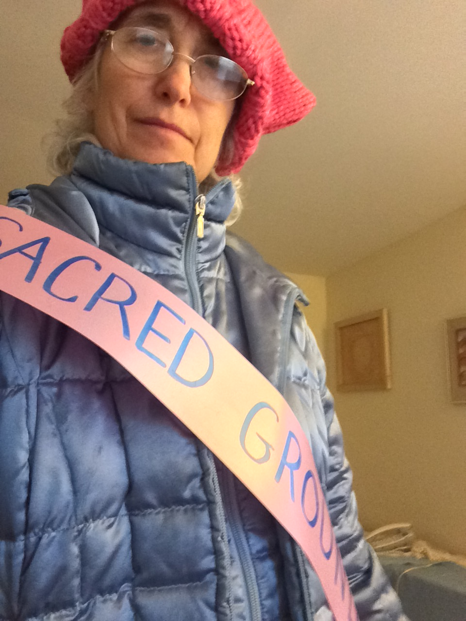 "Photo taken from below, a woman looks down at the camera. She's wearing a blue winter coat, pink ""pussy"" hat, and a paper banner that says ""SACRED GROUND."""